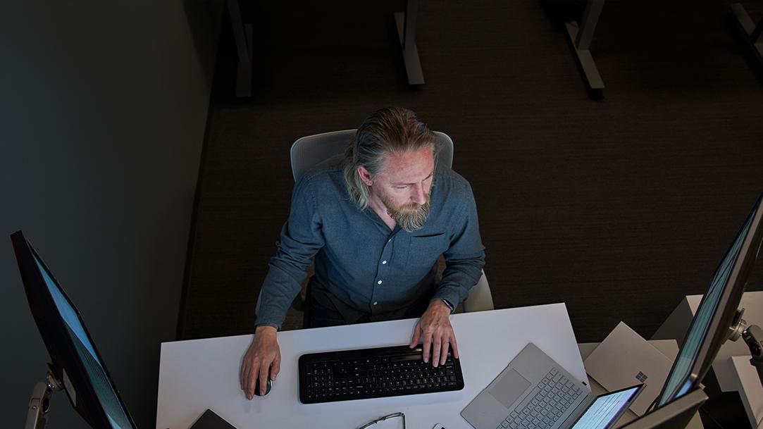 En esta imagen se puede ver a un hombre escibiendo en su computadora, en su escritorio.